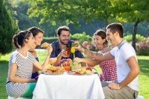 21276643-amigos-disfrutando-de-un-picnic-relajante-sentados-juntos-riendo-y-charlando-en-una-mesa-en-un-parqu